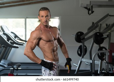 Handsome Mature Man Standing Strong In The Gym And Flexing Muscles - Muscular Athletic Bodybuilder Fitness Model Posing After Exercises