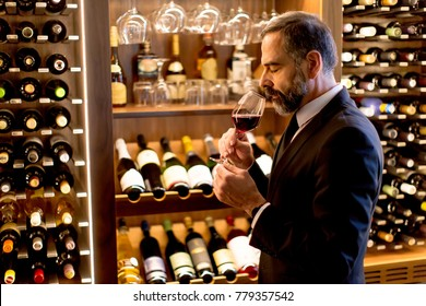 Handsome mature man tasting glass of red wine