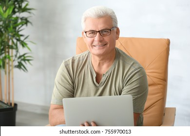 Handsome mature man using laptop at home