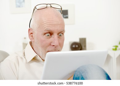 handsome mature man using tablet at home