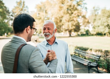 Handsome mature man and young elegant man handshake in the park.