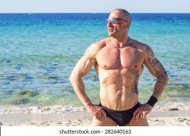 Handsome mature muscle man in swimwear relaxing on sea beach on sunny day