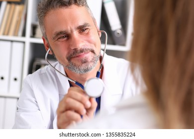 Handsome mature smiling male doctor hold in arm stethoscope head going to listen patient.