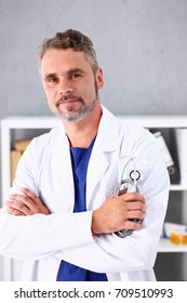 Handsome mature smiling male doctor with arms crossed on chest portrait. Medic store, physical and patient disease prevention, er consultant, 911, profession, pulse measure, healthy lifestyle concept