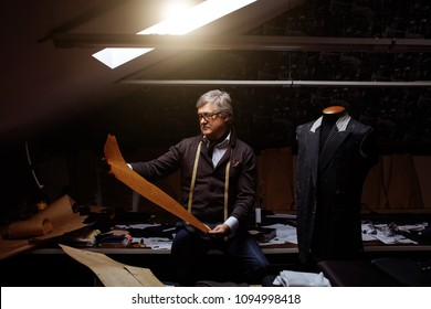 Handsome mature tailor working with cut patterns at garment factory workshop in late evening