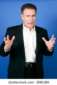 Handsome, mature, white male wearing a black suite and a white shirt gesturing as if telling a joke or story.