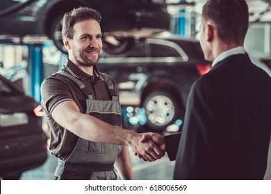 Handsome mechanic and businessman are shaking hands while talking in auto service