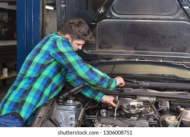 Handsome mechanic talking on the phone while repairing a car.