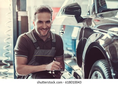 Handsome mechanic in uniform is making notes examining car in auto service