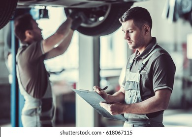 Handsome mechanic in uniform is making notes while his colleague is examining car