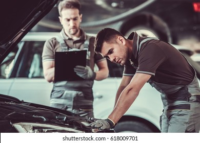 Handsome mechanics in uniform are examining car while working in auto service