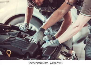 Handsome mechanics in uniform are repairing car while working in auto service
