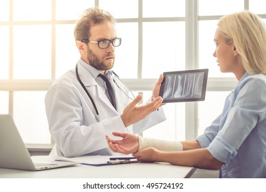 Handsome medical doctor is talking to female patient with injured hand and showing her a X-ray picture on tablet while working in his office