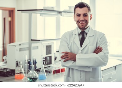 Handsome medical doctor in white coat is looking at camera and smiling while standing in laboratory