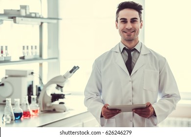 Handsome medical doctor in white coat is using a digital tablet, looking at camera and smiling while standing in laboratory