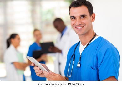 handsome medical surgeon with tablet computer in hospital