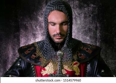 Handsome medieval knight in suit of armour with beard and sword, looking down in contemplation