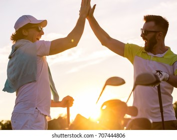 Handsome men are giving high five and smiling when meeting on a golf course