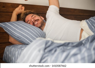 Handsome men waking up and yawning in his bedroom