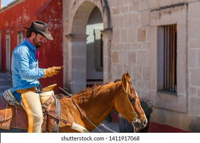 A handsome Mexican Charro poses in front of a hacienda in the Mexican countryside