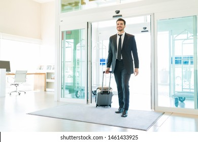 Handsome mid adult businessman pulling luggage while entering hotel lobby