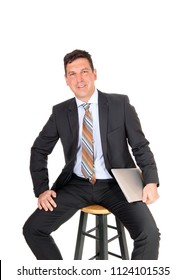 A handsome middle age business man sitting on a chair and smiling 