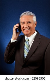 Handsome middle age business man wearing a suit with a wireless telephone on a blue background.