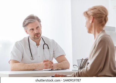 Handsome middle age doctor and female patient at hospital office