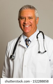 Handsome middle age doctor with lab coat and stethoscope on a gray background.