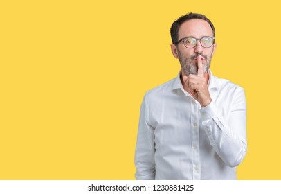 Handsome middle age elegant senior business man wearing glasses over isolated background asking to be quiet with finger on lips. Silence and secret concept.