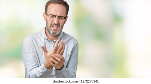 Handsome middle age elegant senior man wearing glasses over isolated background Suffering pain on hands and fingers, arthritis inflammation