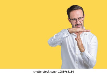 Handsome middle age elegant senior business man wearing glasses over isolated background Doing time out gesture with hands, frustrated and serious face
