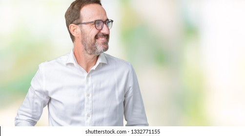 Handsome middle age elegant senior business man wearing glasses over isolated background looking away to side with smile on face, natural expression. Laughing confident.