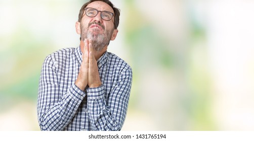 Handsome middle age elegant senior business man wearing glasses over isolated background begging and praying with hands together with hope expression on face very emotional and worried. Asking