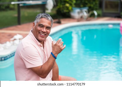 Handsome middle age hispanic man outdoor lifestyle by a swimming pool in a home setting.