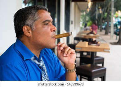 Handsome middle age Hispanic man smoking a cigar.
