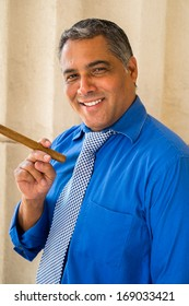 Handsome middle age Hispanic man smoking a cigar outdoors in a urban setting.