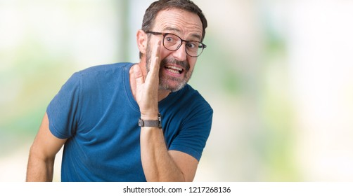 Handsome middle age hoary senior man wearin glasses over isolated background hand on mouth telling secret rumor, whispering malicious talk conversation