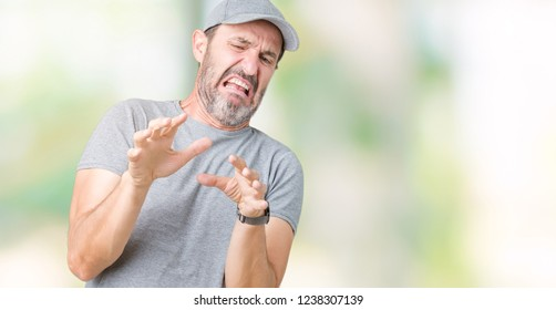 Handsome middle age hoary senior man wearing sport cap over isolated background disgusted expression, displeased and fearful doing disgust face because aversion reaction. With hands raised. Annoying