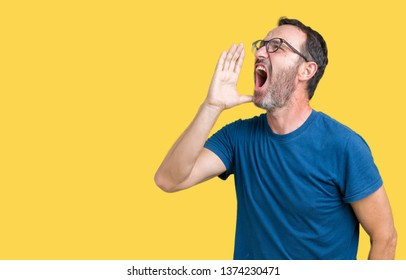 Handsome middle age hoary senior man wearin glasses over isolated background shouting and screaming loud to side with hand on mouth. Communication concept.