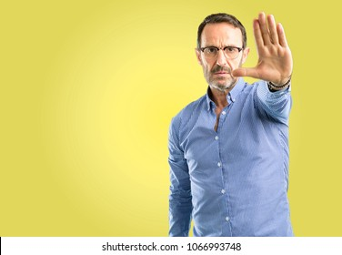 Handsome middle age man annoyed with bad attitude making stop sign with hand, saying no, expressing security, defense or restriction, maybe pushing