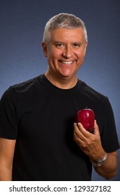 Handsome middle age man with an apple in a studio portrait.