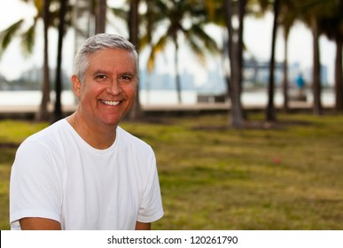 Handsome middle age man in casual clothing enjoying a park setting.
