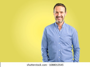 Handsome middle age man confident and happy with a big natural smile looking at camera