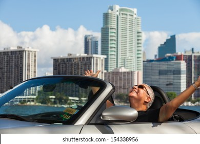 Handsome middle age man in a convertible automobile with a downtown skyline background.