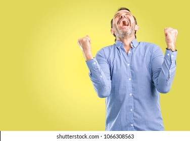 Handsome middle age man happy and excited expressing winning gesture. Successful and celebrating victory, triumphant