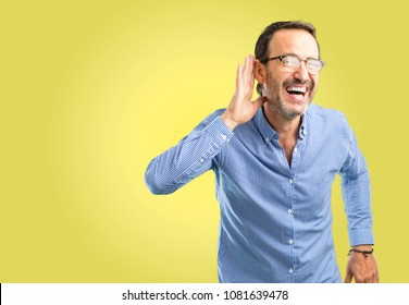 Handsome middle age man holding hand near ear trying to listen to interesting news expressing communication concept and gossip