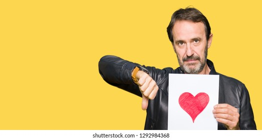 Handsome middle age man holding paper with red heart with angry face, negative sign showing dislike with thumbs down, rejection concept