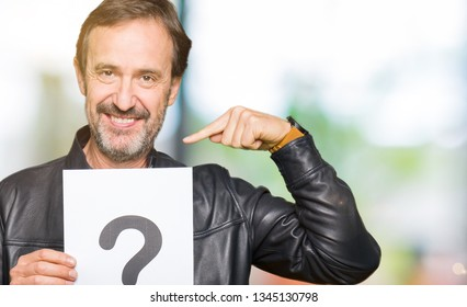 Handsome middle age man holding paper with question mark with surprise face pointing finger to himself