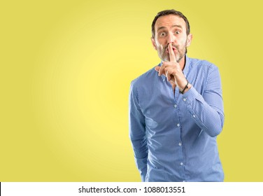 Handsome middle age man with index finger on lips, ask to be quiet. Silence and secret concept